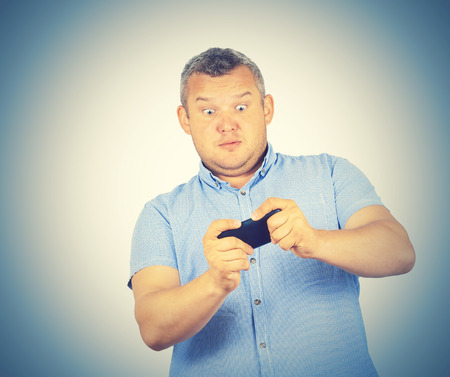 fat man looks at the phone. Playing on a smartphone. Bad news. Emotions.