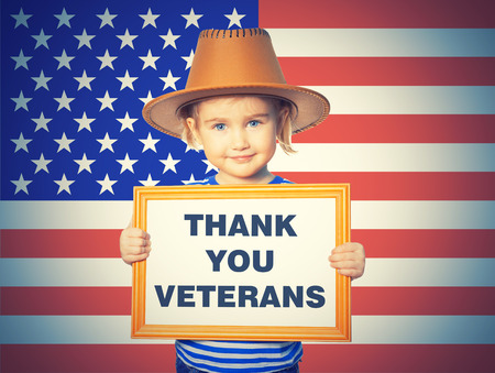 Little Funny girl in striped shirt with blackboard. Text THANK YOU VETERANS.On background of  American flag