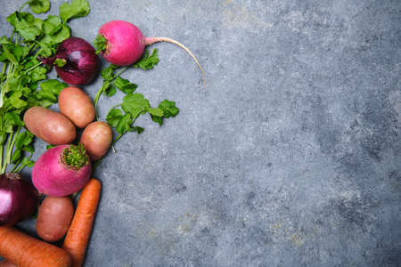 Photo for Turnip, cilantro, potatoes, carrots and red onions on a dark background - Royalty Free Image