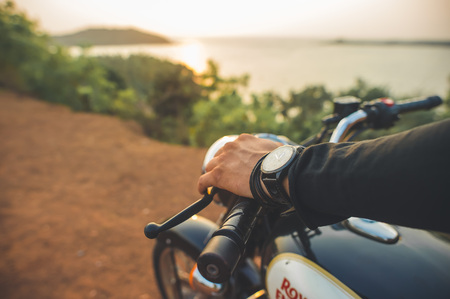 India, Goa -April 6, 2017: Man's hand with a watch on the helm of the Royal Enfield motorcycle during sunset.