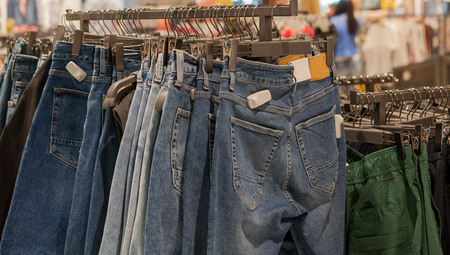 Jeans shorts on the store shelf. Fashionable clothes on the shelves in the store. Jeans hanging on the vests in the fashion store. Showcase, sale, shopping.