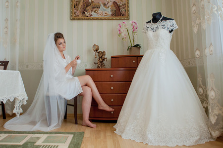 The charming bride with bridesmaids stands near wedding dress. Bridal wedding morning preparation.