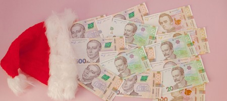 Ukrainian hryvnia banknotes coming out of Santa Claus hat on a pink background. Christmas Shopping Concept.