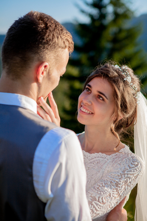 Foto de Newlyweds smile and hug each other among the meadow on top of the mountain. Wedding walk in the woods in the mountains, the gentle emotions of the couple, photo for Valentine's Day. - Imagen libre de derechos