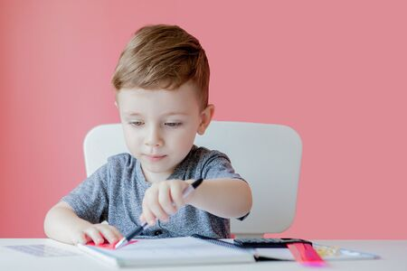 Photo pour Portrait of cute kid boy at home making homework. Little concentrated child writing with colorful pencil, indoors. Elementary school and education. Kid learning writing letters and numbers. - image libre de droit