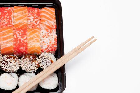 Photo pour Big sushi set ib black plastic box on white background, top view close up, copy space. - image libre de droit