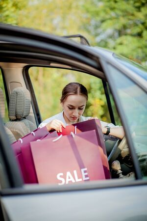 Photo for Woman with her shopping bags into the car - shopping concept - Royalty Free Image