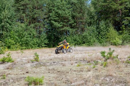 Man riding a yellow quad ATV all terrain vehicle on a sandy forest. Extreme sport motion, adventure, tourist attraction