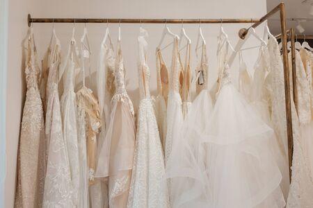 Photo pour Assortment of dresses hanging on a hanger on the background studio. Fashion wedding trends. Interior of wedding shop. - image libre de droit
