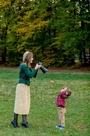 Photo for Woman photographer photographing the child to spend outside in the park. - Royalty Free Image