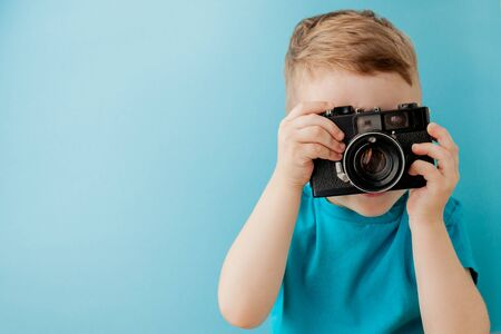 Photo for Little boy with an old camera on a blue background. - Royalty Free Image