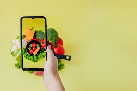 Photo for Girl taking picture of vegetarian food on table with her smartphone. Vegan and healthy concept - Royalty Free Image