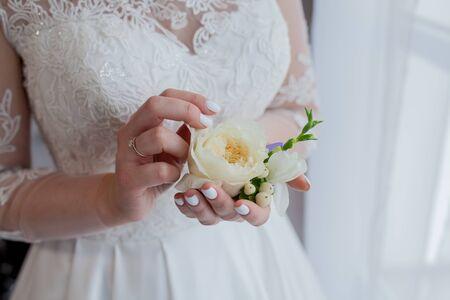 Photo pour Close-up of the bride's hands holds a boutonniere. boutonniere with red rose. - image libre de droit