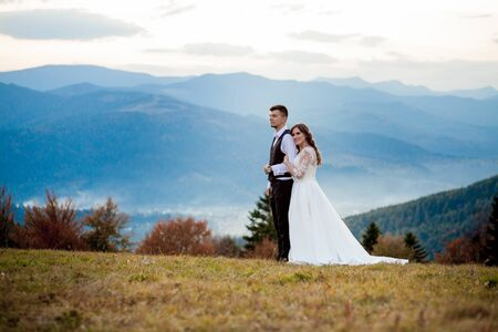 Photo pour Beautiful wedding couple, bride and groom, in love on the background of mountains. The groom in a beautiful suit and the bride in a white luxury dress. Wedding couple is walking. - image libre de droit