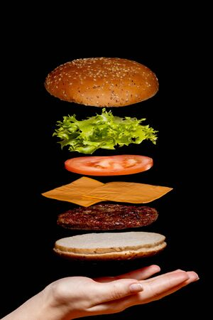 Photo pour Flying ingredients burger or cheeseburger on a small wooden cutting board isolated on a dark background. Burger floating in the air above the table. Space for text. - image libre de droit