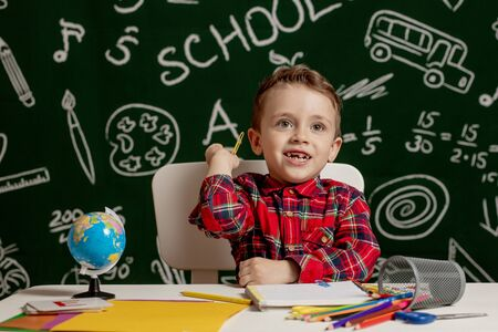 Emotional school boy sitting on the desk with many school supplies. First day of school. Kid boy from primary school. Back to school. Child from elementary school