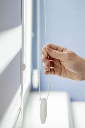 Photo pour Man testing cassette roller blinds on windows - image libre de droit