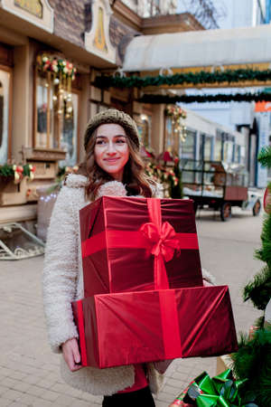 Photo for Portrait Happy good-looking woman is holding gift box in her hands and smiling while standing outdoors. Beautiful happy girl posing with Christmas presents. New Year preparation - Royalty Free Image
