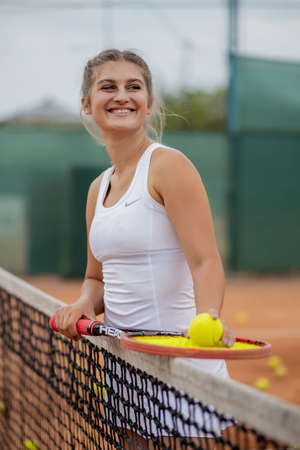 Photo for Happy smiling girl is chilling near tennis net at tennis court with racquet in hands - Royalty Free Image