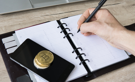 Notebook of bitcoin miner. Bitcoin golden coin on a smart phone and on a notebook with a pen. Mans hand with a pen ready for write his income from the trading mining of bitcoin. Bussiness.