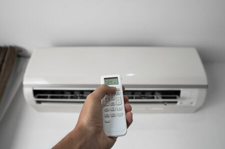 Foto de Mans hand using remote controler. Hand holding rc and adjusting temperature of air conditioner mounted on a white wall. Indooor comfort temperature. Health concepts and energy savings. - Imagen libre de derechos