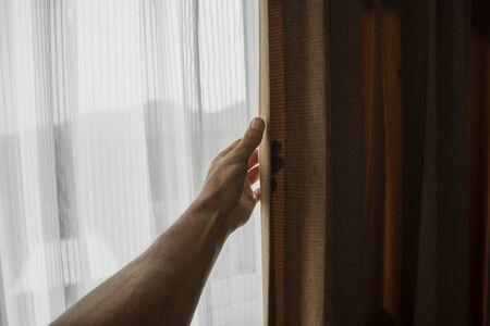 Photo pour Men hand opening curtain in bed room. - image libre de droit