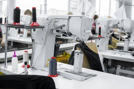 Photo pour Professional sewing machine with black thread on a shoes factory - image libre de droit
