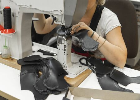 Photo pour Sewing machine in a leather workshop in action with hands working on a leather details for shoes. Womens hands with sewing machine at shoes factory. - image libre de droit