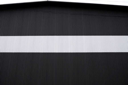 Photo pour Black and white corrugated iron sheet used as a facade of a warehouse or factory. Texture of a seamless corrugated zinc sheet metal aluminum facade. Architecture. Metal texture. - image libre de droit
