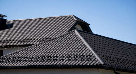 Photo pour Brown corrugated metal profile roof installed on a modern house. The roof of corrugated sheet. Roofing of metal profile wavy shape. Modern roof made of metal. Metal roofing. - image libre de droit