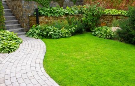 Photo pour Garden stone path with grass growing up between the stones  - image libre de droit