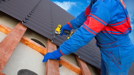 Photo for Man worker uses a power drill to attach a cap  metal roofing job with screws. - Royalty Free Image
