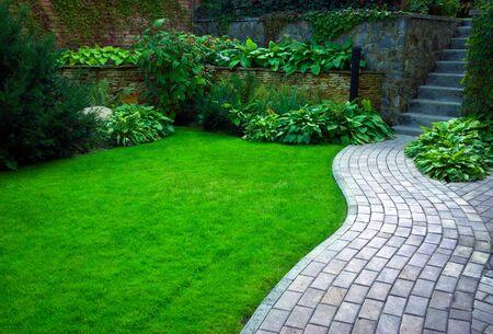 Foto de Garden stone path with grass growing up between the stones.Detail of a botanical garden. - Imagen libre de derechos