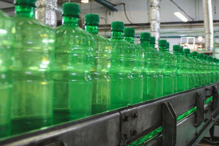Conveyer belt with green plastic bottles for beverages. Perspective view. concept of producing clean bottled water