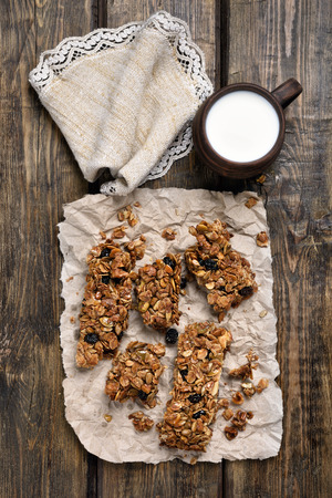 Cereal bars on paper and cup of milk on wooden background, top view
