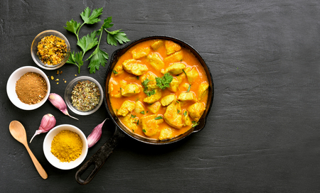 Photo pour Chicken curry on black stone background with copy space. Top view, flat lay - image libre de droit