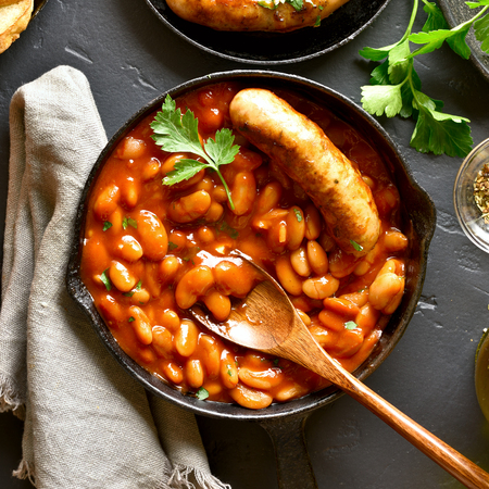 Photo pour Close up of baked white beans in tomato sauce with sausage in frying pan over black stone background. Top view, flat lay - image libre de droit