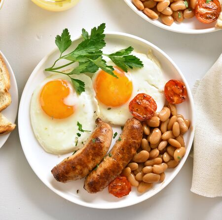 Photo pour Close up of breakfast with fried eggs, sausages, beans, tomatoes, greens on plate over white stone background. Top view,flat lay - image libre de droit
