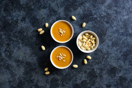 Photo for Peanut sauce in bowl over blue stone background with free text space. Top view, flat lay - Royalty Free Image