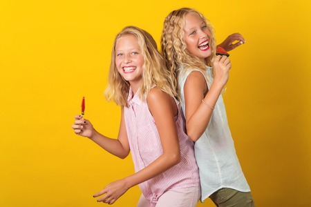 Photo for Twins teenager girls having fun together, isolated on the yellow background. - Royalty Free Image
