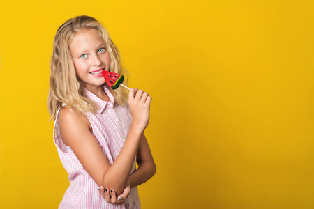 Handsome young girl having fun with lollipop over the yellow background, copy spaceの写真素材