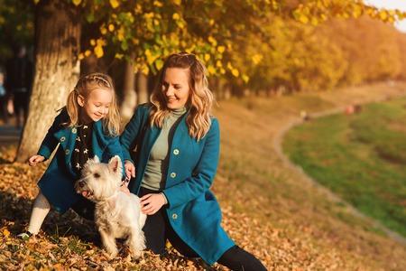 Foto de Mother and little daughter walking with dog in autumn. Outdoors portrait of happy family. Autumn fashion. Stylish little daughter and her beautiful mother. Happy childhood - Imagen libre de derechos