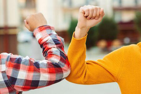 Photo pour Friends bump elbows outdoors. Coronavirus epidemic. Health care concept. Social distancing. Elbow bump. New greeting style. Coronavirus quarantine. Fight coronavirus. - image libre de droit