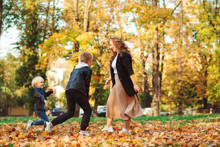 Photo pour Mother with children throwing autumn leaves in a park. Autumn holidays. Mom and her sons having fun outdoors. Fashionable family walking in autumn nature. Family, fashion and lifestyle - image libre de droit