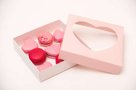 Photo for Macaroons cookies in box on white table. French cookies in gift box. Sweet macarons in gift box. Traditional french colorful macarons. Valentine's day gift. Pink macarons in the heart shape. - Royalty Free Image