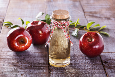 Apple cider vinegar and red apples over rustic wooden backgroundの写真素材