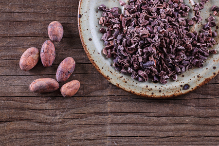 Foto für Raw Cacao Nibs in a ceramic plate and cacao beans over rustic wooden background. Top view - Lizenzfreies Bild