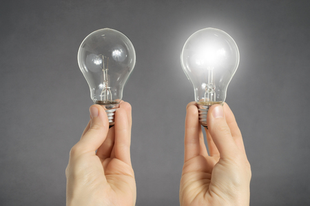 Foto de Decision making concept. Hands holding two light bulbs, one of them is glowing - Imagen libre de derechos