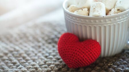 Photo pour Background with gray cup with marshmallows and red heart on knitted napkin. warm drink with grey scarf.. Valentines day concept, mug cup of coffee - image libre de droit