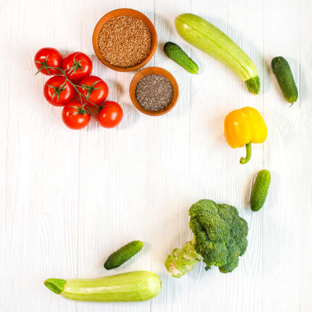 Photo pour Fresh vegetables on a white background. Dietary products on a wooden table. Cucumbers, broccoli, tomato, zucchini and porridge in a wooden plate. - image libre de droit